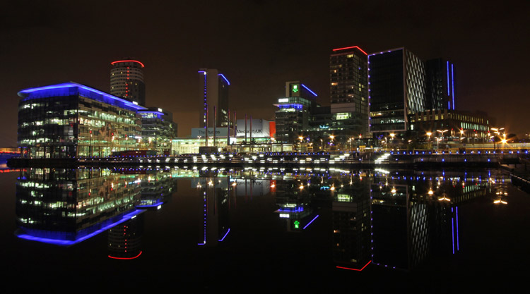 A night time photo of MediaCity, Salford, Manchester showing the neon lights reflecting against the water
