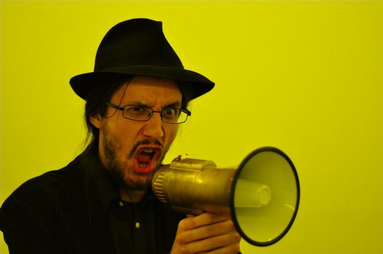 A bearded man shouting through a megaphone - (Photo by Very Quiet)