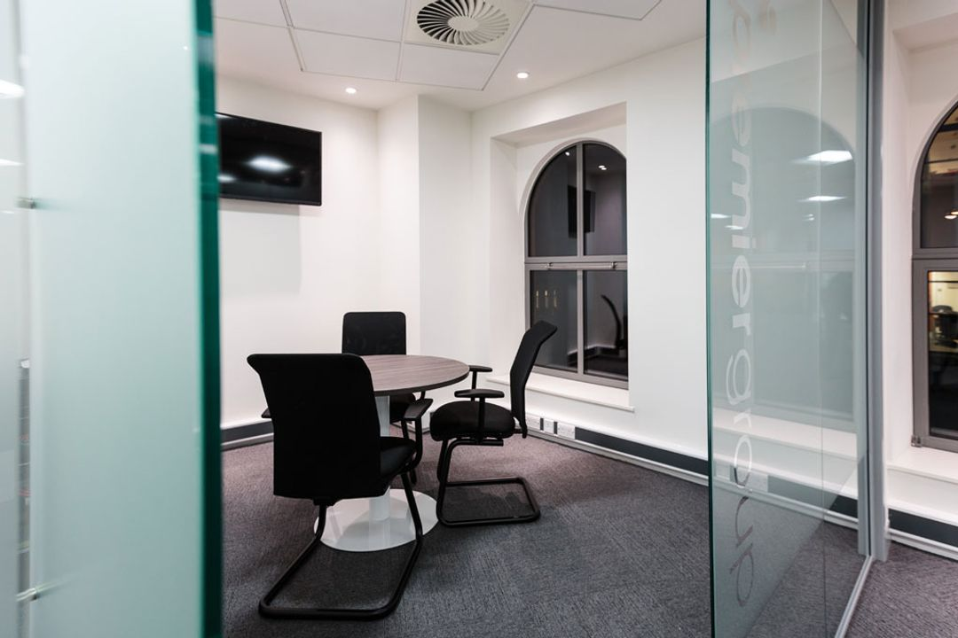 Glass partitioned meeting room with small circular meeting table and chairs - Premier Group, Manchester