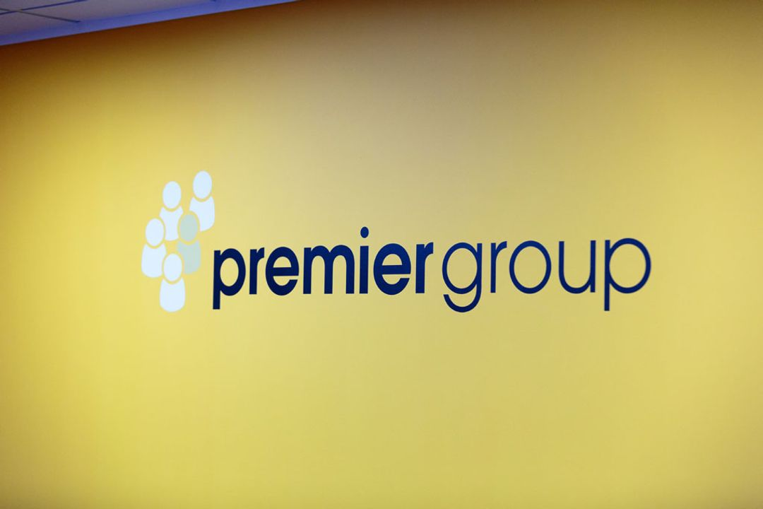 A large mural of the Premier Group recruitment logo branding on a dark yellow office wall backdrop